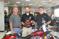 Marty Fischer, American Honda Motor Company dealer representative presents Petersen Motors 50-year as a dealer plaque to Ross Petersen and Russ Dulany.